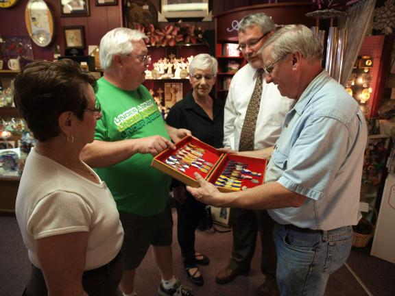 AL ZAGOFSKY/SPECIAL TO THE TIMES NEWS Looking over the 25 duplicate medals of Jim Thorpe's pre-Olympic victories are, from left, Anne Marie Fitzpatrick of the Jim Thorpe Birthday Weekend Committee; Chuck Gentile, sports director at the U.S. Army War…