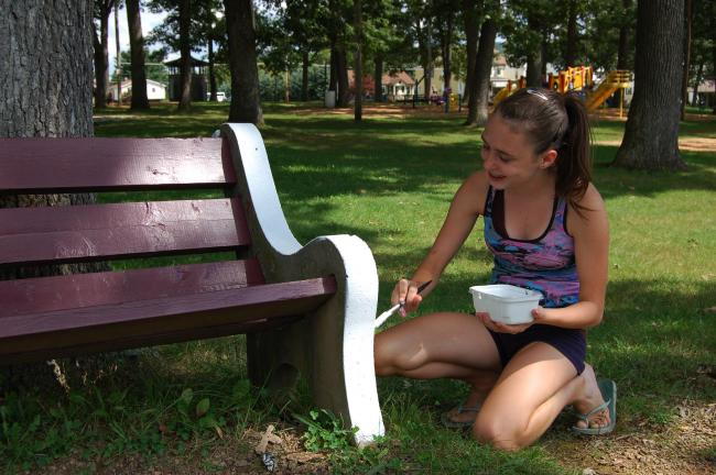 Gail Maholick/TIMES NEWS Cassandra Rehnert, 14, of Lehighton, paints a bench at the Lehighton Grove. Cassandra is earning her Silver Award by painting benches and power washing play equipment at the Grove playground in Lehighton.