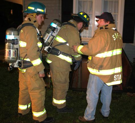 ANDREW LEIBENGUTH/TIMES NEWS Tamaqua firefighters investigate the outside of the home for the cause of the fire.