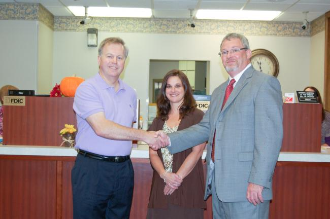 CHRIS PARKER/TIMES NEWS Lansford Alive President Mark Sverchek, left, shakes hands with Jim Thorpe National Bank President Craig Zurn. In the middle is Lansford branch bank manager Monica A. Marshall.
