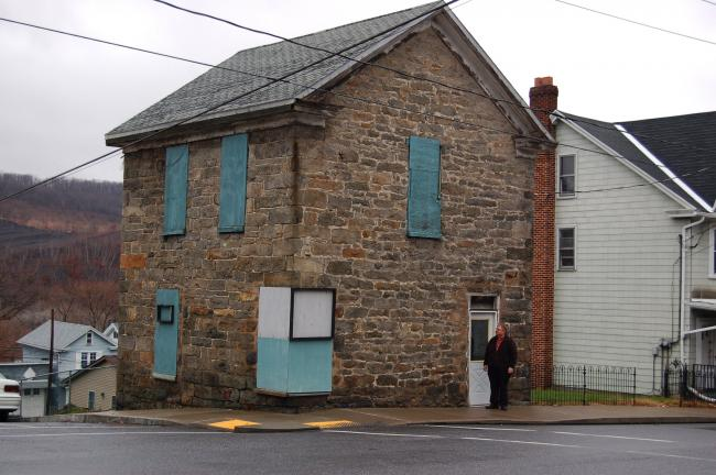 """Dale Freudenberger of the Lehigh and Delaware National Heritage Corridor surveys the outside of the """"old jail"""" in Lansford, purchased by the Lansford Alive community improvement organization."""