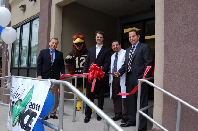CHRIS PARKER/TIMES NEWS Lansford Alive president Mark Sverchek, left, stands with Talon, the Lehigh Valley Steelhawks mascot; Dr. Thomas M. Rocchio; Dr. Joseph S. Saka as Dr. Adam J. Teichman cuts the ribbon to celebrate the opening of PA Foot &…