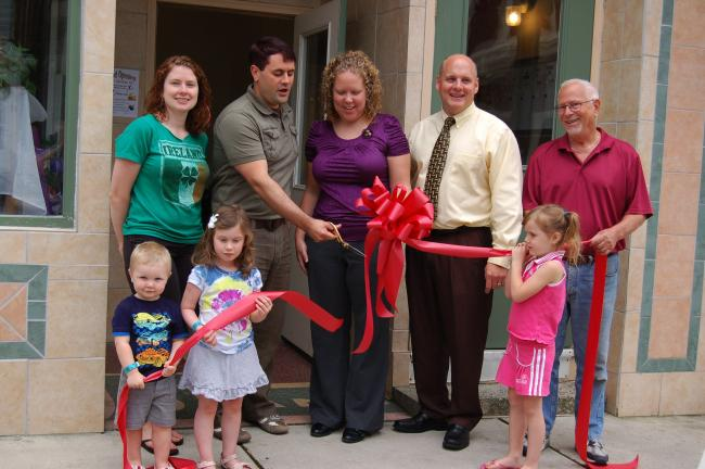 Executive Director Jonathan Rodgers, second from left, cuts the bright red ribbon Friday at a celebration to mark Holistic Therapeutic Outreach Services' grand opening at 50 W. Ridge St., Lansford. In front are Andrew Rodgers, 2, and Zoe Rodgers, 4,…