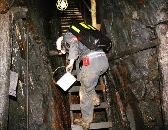 A mine rescuer steps up the steep ladder of an escape chamber of the mine.