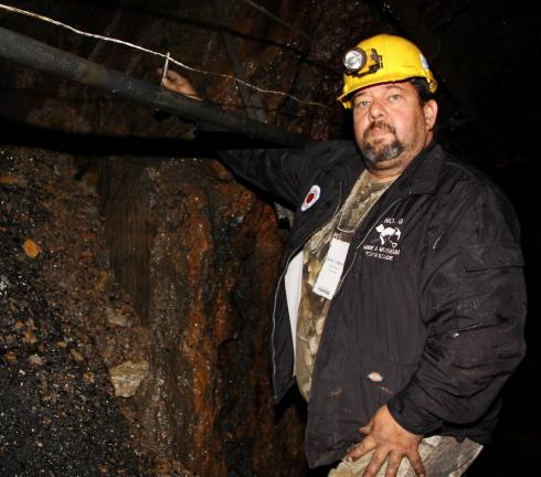 ANDREW LEIBENGUTH/TIMES NEWS Israel Gonzalez, assistant mine manager and electrician, No. 9 Mine and Museum, stands next to a section of the mine tunnel that has exposed a portion of a petrified tree.