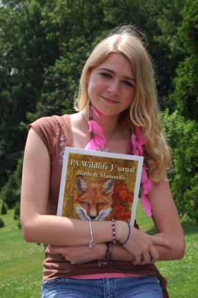 """Jayne Kuehner holds a copy of """"PA Wildlife Journal Birds and Mammals,"""" a book just released that contains two drawings she submitted."""