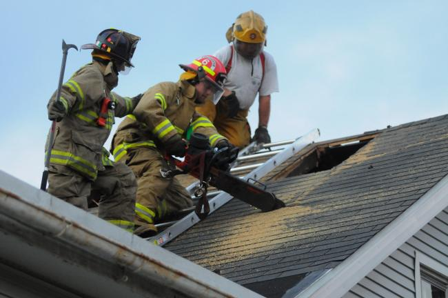RON GOWER/TIMES NEWS Mahoning Valley Fire Company member Tim Schnell, center, cuts a ventilation hole into the roof of a house that is going to be demolished during a joint training session last night for Mahoning and Lehighton fire departments…