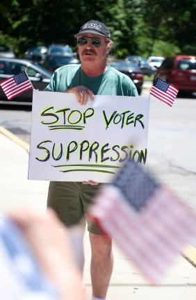 BOB FORD/TIMES NEWS Mike Schirra of Penn Forest Township, holds a sign protesting the new voter ID legislation in front of the Courthouse Annex in Jim Thorpe.