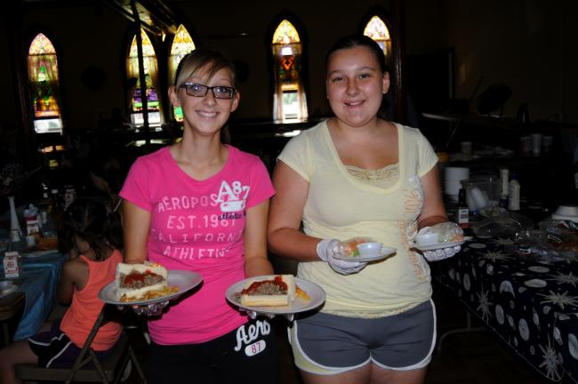 RON GOWER/TIMES NEWS Cortnee Hartman, left, and Breanna Card serve meals during the summer lunch program at the Summit Hill Heritage Center. A total of 1,922 lunches were served during the first year of the program.