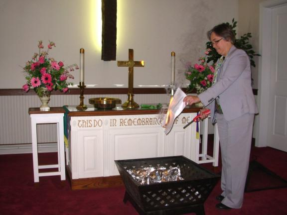 ADELE R. ARGOT/SPECIAL TO THE TIMES NEWS Pastor Robin Fisher burns the symbolical papers of the church mortgage having been satisfied. It was a time of celebration.