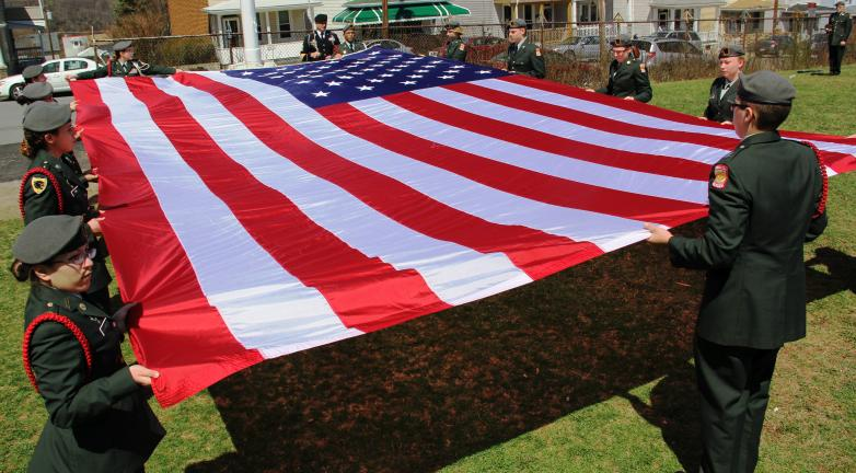ANDREW LEIBENGUTH/TIMES NEWS Members of Panther Valley's JROTC unfold a large American Garrison-sized flag in preparation for it's ceremonial raising at the old Coaldale High School.