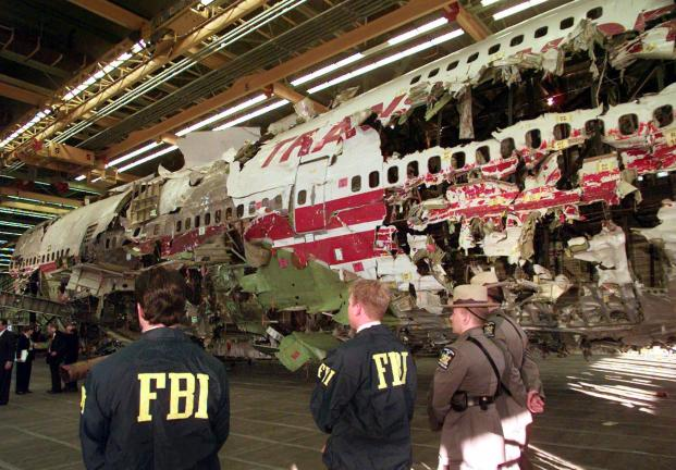 AP PHOTO In this Nov. 19, 1997 file photo, FBI agents and New York state police guard the reconstruction of TWA Flight 800 in Calverton, N.Y. Flight 800 exploded and crashed July 17, 1996 while flying from New York to Paris, killing all 230 people…