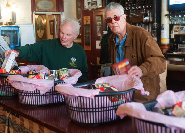 BOB FORD/TIMES NEWS Carbon County Ancient Order of Hibernian members Matthew P. Stinson Jr., left, and Dr. Clement McGinley help fill baskets Saturday morning at Molly Maguires Pub and Steakhouse. The baskets, which contain all that is needed for an…