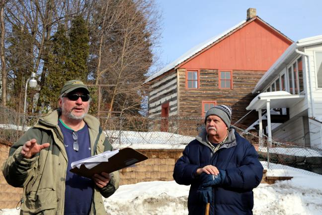 """The Molly Maguire Meander walking tour ended in Tamaqua's East End with a visit to the 1801 Burkhardt Moser log home, the first house built in Tamaqua. Shown are tour guide """"Porcupine Pat"""" McKinney and Schuylkill County Judge John Domalakes."""