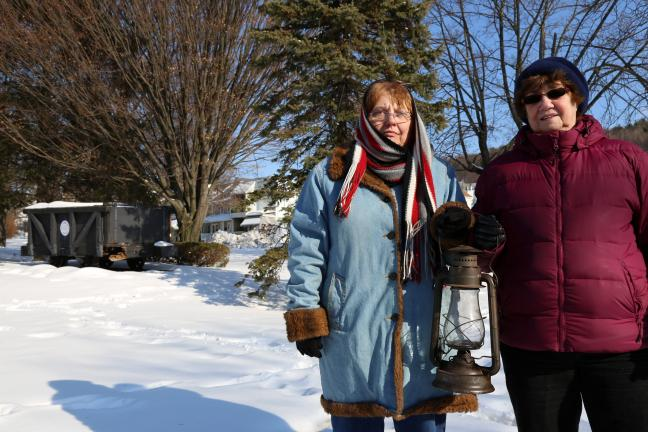DONALD R. SERFASS/TIMES NEWS  Marie Ondrus, left, and Irma Leibensperger carry an oil lamp, symbolic of lighting the way for a bright future at Lansford's Kennedy Park, which will mark its 40th anniversary next year but is in need of a face-lift.