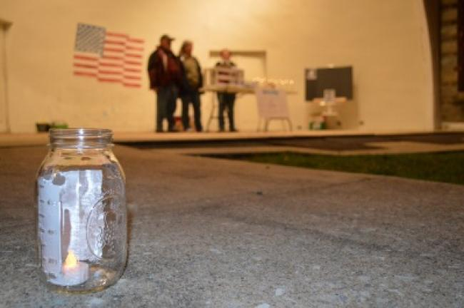 Mason jars with tea lights line the walkways of the Lehighton band shell for the suicide vigil Saturday. KELLEY ANDRADE/TIMES NEWS
