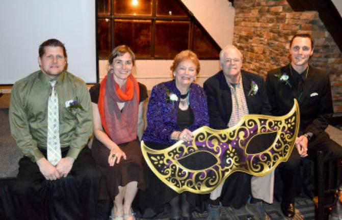 Chamber award winners Christopher Ondrus, Maya Kowalck, Joan Turko, Slate Altenburg and Sky Fogal pose together with the dinner's giant Mardi Gras themed mask. KELLEY ANDRADE/TIMES NEWS