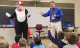 """Above: The Cat in the Hat, played by Brandon Pearsall, a project manager with the Walmart Realty Field Execution team, and Shull-David Elementary School principal Aaron Sebelin discuss the book """"Cat in the Hat"""" with kindergarten students after…"""