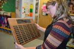 LISA PRICE/TIMES NEWS Tara Stauffenberg looks at a dusty plaque from the former Coaldale High School trophy case.