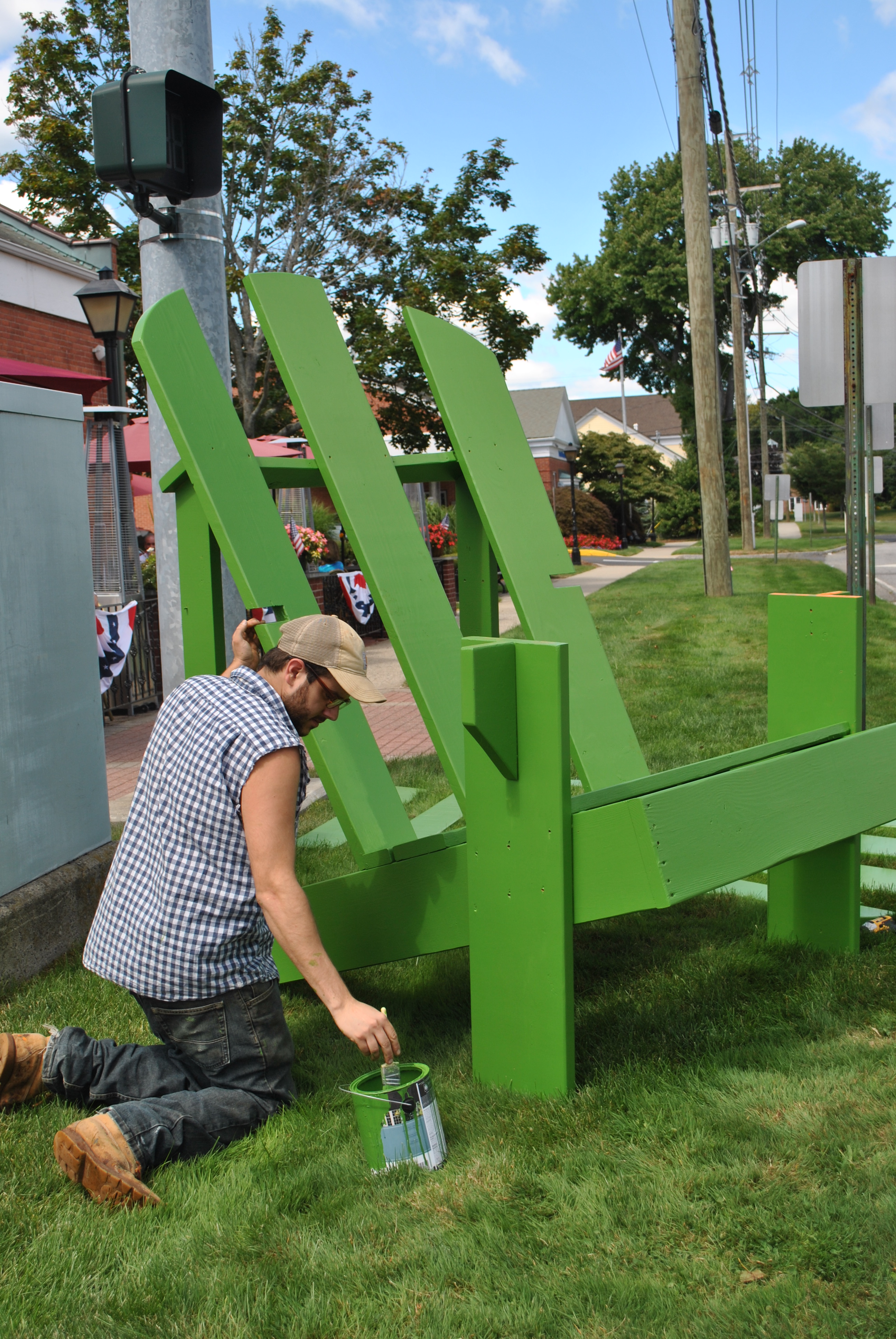 Doug Calderone applies a coat of green paint to a giant Adirondack chair outside of My Place Restaurant and Pizza Friday morning August 29. & Enough Chair To Host The Neighborhood | The Newtown Bee