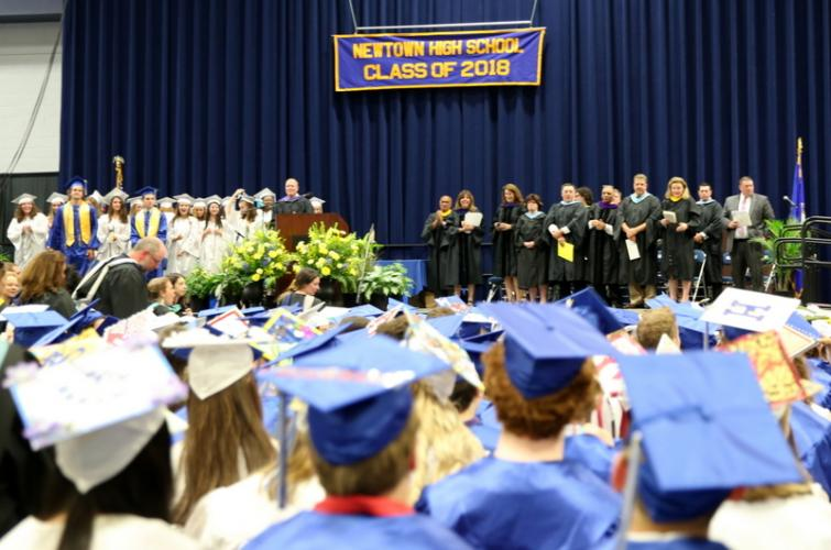 People on stage for the June 18 Newtown High School commencement ceremony at Western Connecticut State University's O'Neill Center stand to applaud the NHS Class of 2018 members seated in front of them.  (Bee Photo, Hallabeck)