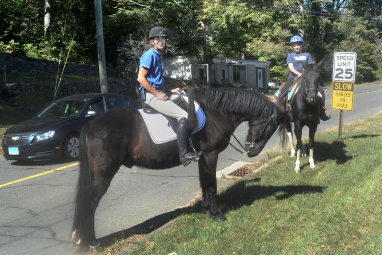 Brenda Majeski and her horse, Majic, right, and Barbara Gaydosh and her horse, Skye, along the side of Huntingtown Road as traffic passes. (Bee Photo, Hutchison)