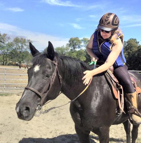 Dee Davis, on her horse, Mamosa, wants drivers to respect the rights of equestrians to ride on the road.