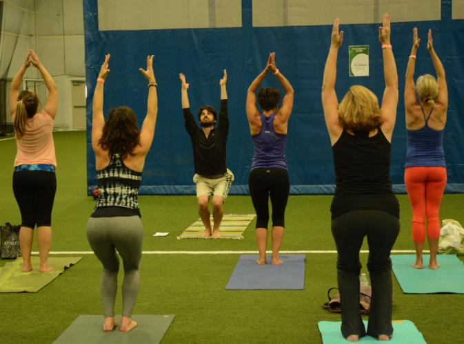Under the guidance of yoga instructor Brian Pontolilo, third from left, a group of yoga participants demonstrates the chair pose. The instructional session was one of many held at the Newtown Yoga Festival.