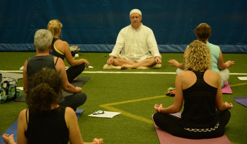 Yoga instructor Chris Smith, center, presides during a session of Kundalini yoga at the Newtown Yoga Festival. The meditative Kundalini yoga seeks to energize and revitalize the body.
