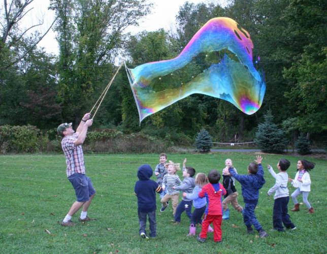 Travis Tietjen, left, made some awfully large soap bubbles for the amusement of tots attending Trinity Day School's Fall Family Festival on Saturday, September 30, at Castle Hill Farm, Route 302. The children and their parents took part in rustic…