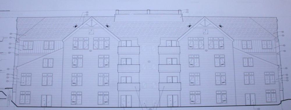 This elevation drawing shows a rear view of a 28-unit apartment house at Hunters Ridge. The structure has walkout basements and balconies. The complex would have 648 parking spaces.