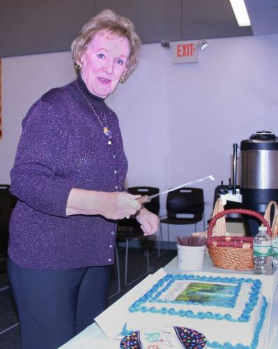 Outgoing First Selectman Pat Llodra cuts a cake in her honor at a town coffee-and-cake event to fete her on November 28. Several dozen town employees gathered to wish her well on her retirement.  (Bee Photo, Gorosko)