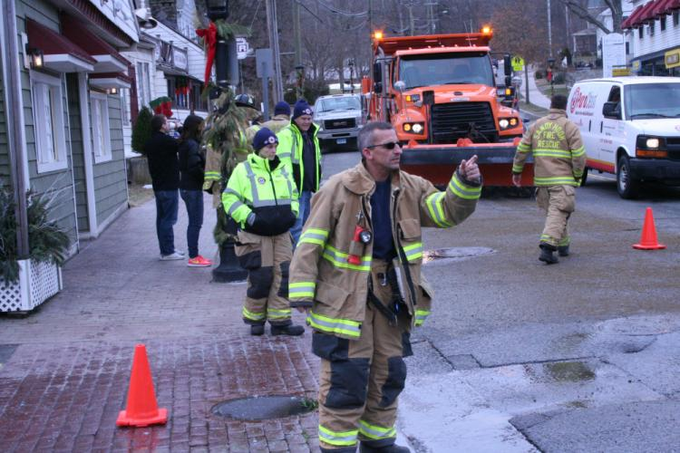 "Sandy Hook Volunteer Fire & Rescue Company firefighter Richard ""Archie"" Paloian gestures to a motorist midday on Monday, January 15, in Sandy Hook Center, where a liquid was bubbling up from beneath Church Hill Road.  (Bee Photo, Gorosko)"