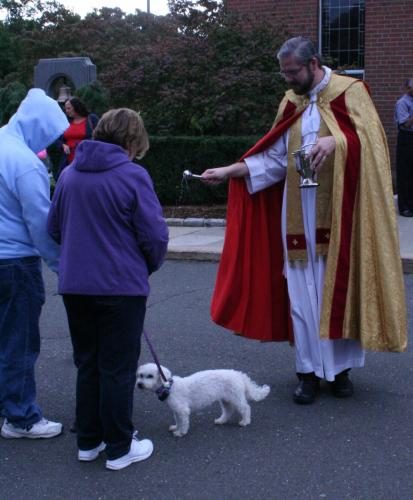 At The Blessing of The Animals, which is held to celebrate the Feast of St Francis, Rev Kuczynski puts some holy water on a small dog in front of St Rose Church.   (Bee Photo, Gorosko)