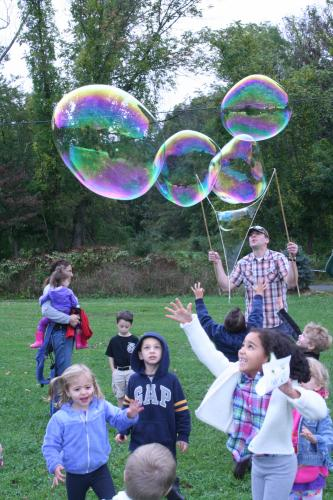 Happy kids from Trinity Day School frolicked as Travis Tietjen created huge soap bubbles that wafted across the rural landscape at Castle Hill Farm.  (Bee Photo, Gorosko)