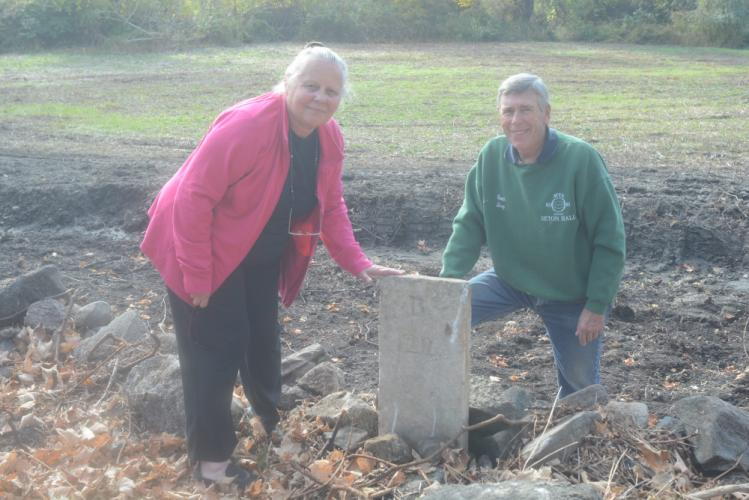 Tina and Terry Banhardt stand with an early 1800s mile marker that was uncovered by public works crief chief Milton Adams. The marker is near their Currituck Road property. (Bee Photo, Hutchison)