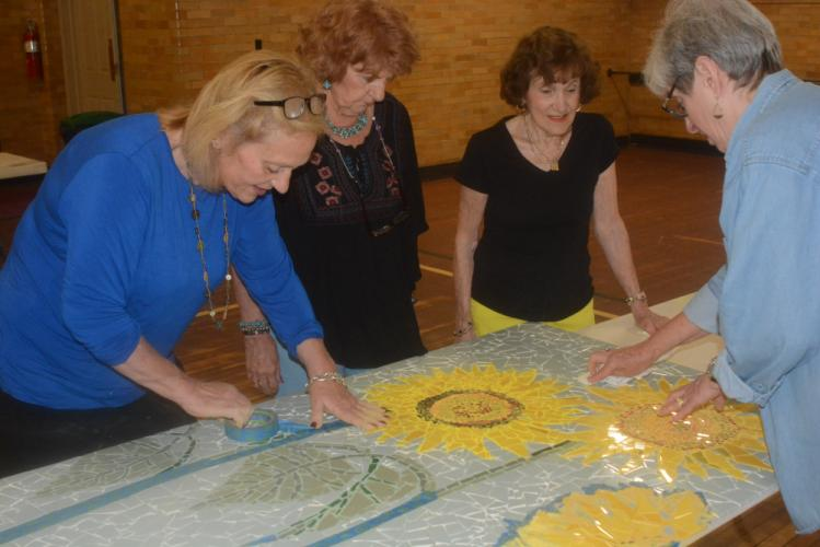 Joanne Hunter, of The Art Spot, designer of the mural, works with volunteers to put the mural together. Pictured are, from left, Ms Hunter, Dottie Dellapiano, Marianne Muskus, and Karen Jackson (with back to camera).  (Bee Photo, Hutchison)