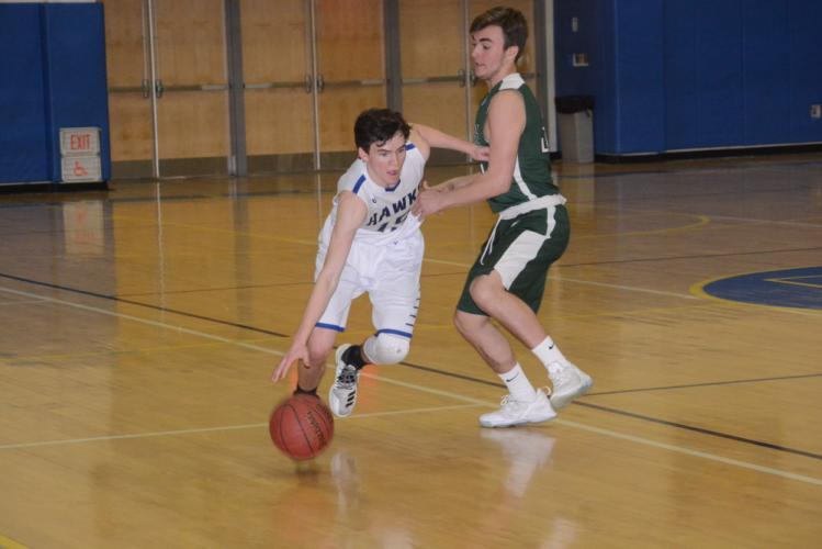 Nick Weiland goes low to get past a New Milford defender during Newtown's 61-48 win on February 6. (Bee Photo, Hutchison)