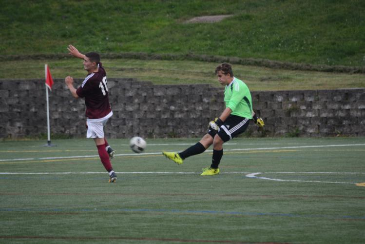 Goalkeeper CJ Trivers sends the ball up the field as a Bethel player attempts to get in the way. (Bee Photo, Hutchison)