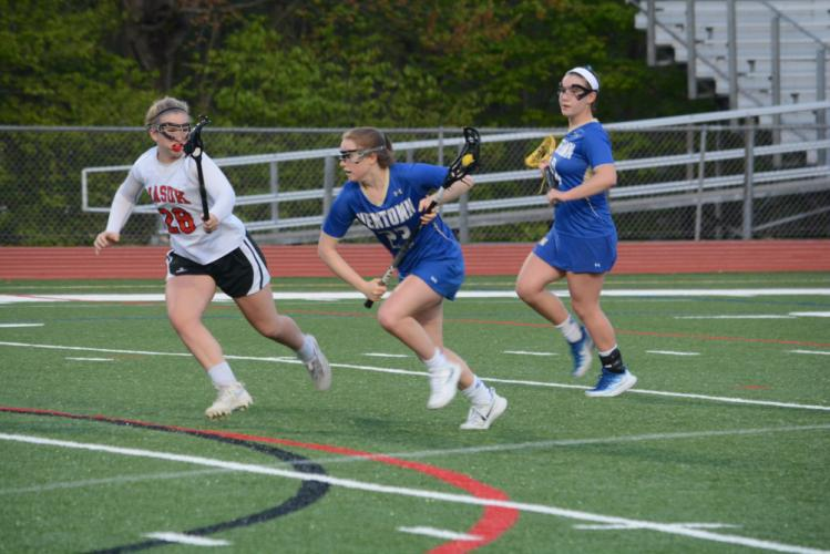 Julia Sughrue runs toward the Masuk goal during Newtown's 12-6 win on May 11. Teammate Alex Futterman looks on. Sughrue and Futterman both scored five goals in a 12-11 double overtime win at Guilford two days later. Sughrue had the game-winner. (Bee…