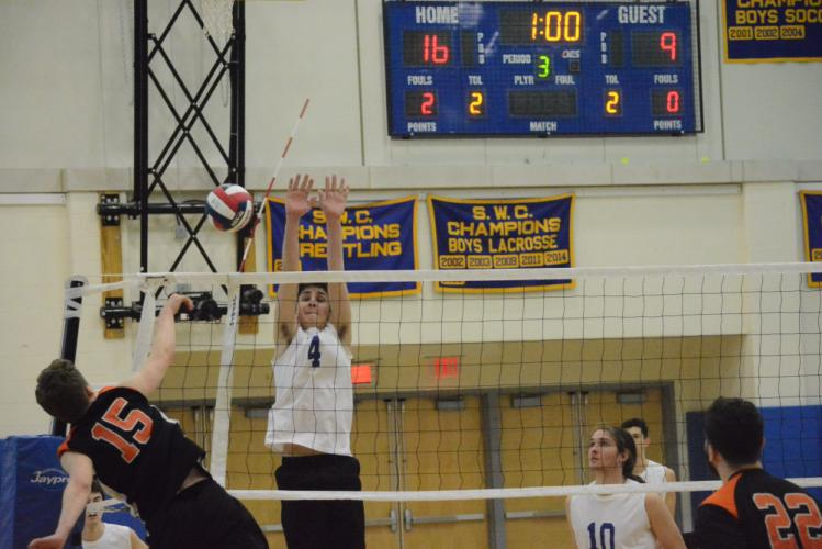 Eric Moore goes up for a block during Newtown's first match against Shelton this spring. (Bee Photo, Hutchison)