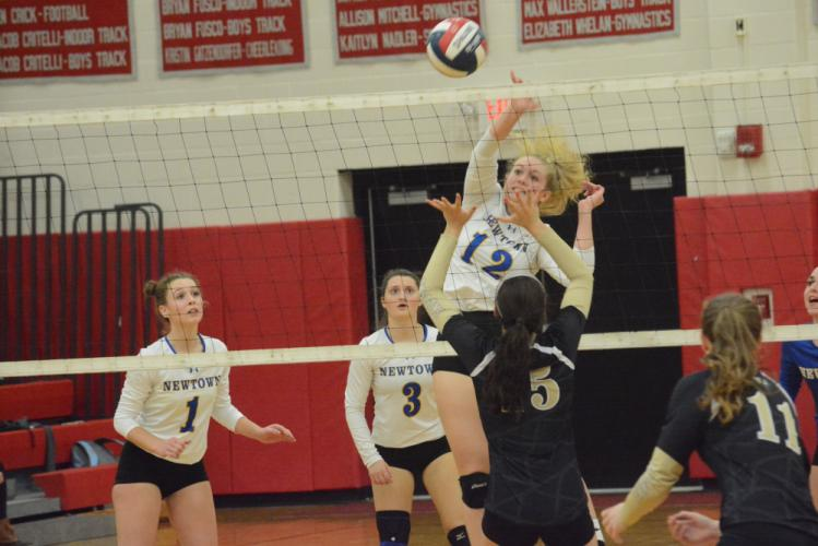 Erin Mitchell smashes the ball for a point as Kim Buttery (No. 1) and Mollie Goudy look on. (Bee Photo, Hutchison)