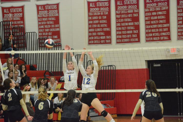 Kim Buttery (No. 1) and Erin Mitchell go up for a block during the conference tourney. Newtown won its state playoff opener. (Bee Photo, Hutchison)