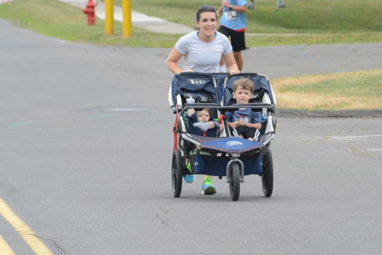 Jenny Edwards pushes her children and future runners, Carson and Owen, toward the finish line of the 5K. (Bee Photo, Hutchison)