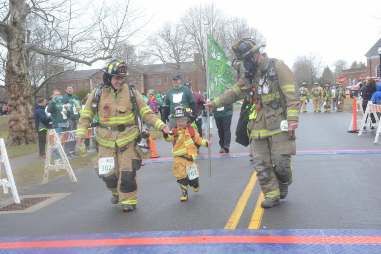 Sandy Hook firefighter Peter Barresi, left, and Washington firefighter Jeff Kozo help Kozo's son Jace (clearly a firefighter in training), across the finish. Kozo challenged the Sandy Hook firefighters to run the 5K in the first year of the event,…