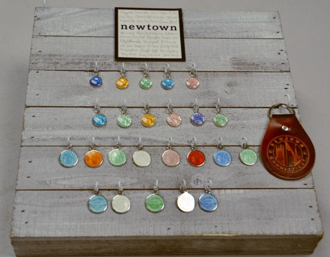 5 Janes sells Newtown and Southbury inspired pendants in a variety of colors, as well as a Newtown leather key fob, pictured right. (Bee Photo, Silber)
