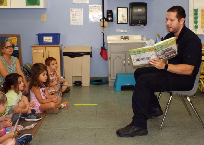 Newtown Volunteer Ambulance Corps member Dan Cragin read a story about ambulances to the children at Misty Morning Children's Center on Tuesday, October 12, for Safety Week. (Bee Photo, Silber)
