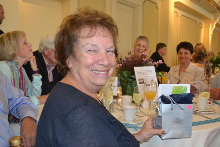 Cathy Mazzariello received a roar of applause from her table at the Newtown Giving Circle's 29th Annual Summer Breakfast after winning the raffle drawing from Avancé Day Spa, which she plans to share with her daughter, Gina Mazzariello. (Bee…