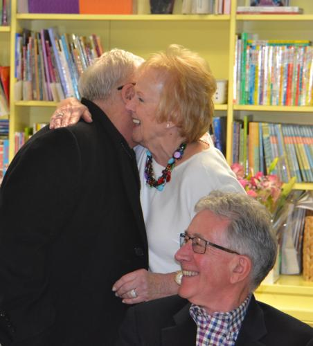 Former First Selectman Pat Llodra hugs Monsignor Robert Weiss of St Rose Church, as her husband Bob Llodra looks on, during the high tea event at the Children's Adventure Center. (Bee Photo, Silber)