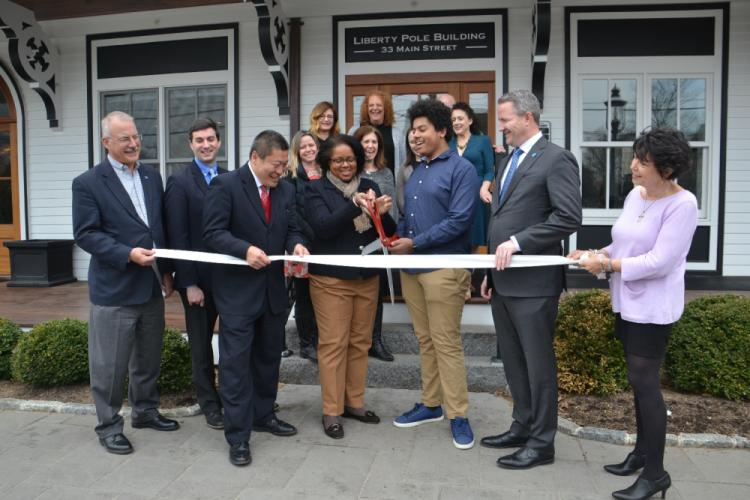 Kristie Bell Petershack holds the ceremonial ribbon cutting scissors with her son, Brooks, to officially open her company Imagine Grace Photography at its new studio at 33 Main Street on April 12. She was also joined by First Selectmen Dan Rosenthal…